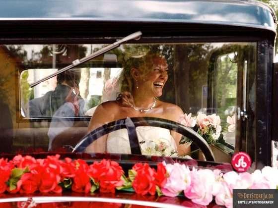 bryllupsfotografering brud i veteranbil griner