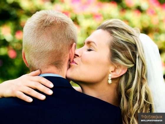 bryllupsfotograf brud kysser gom på øreflip