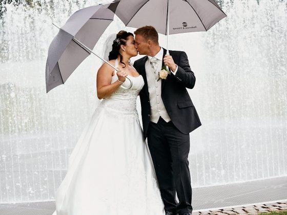 bryllup fotograf brudepar kysser under paraplyerne