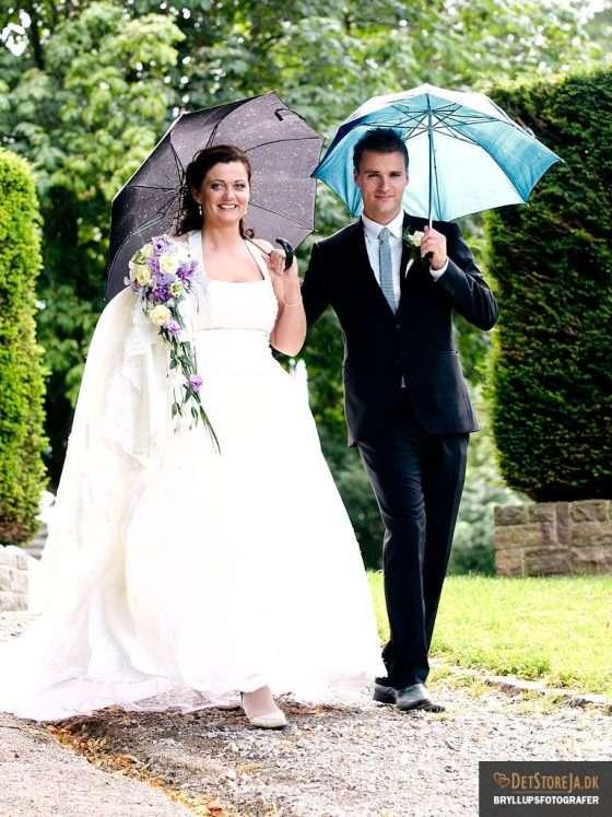 bryllupsbillede gående brudepar med paraplyer