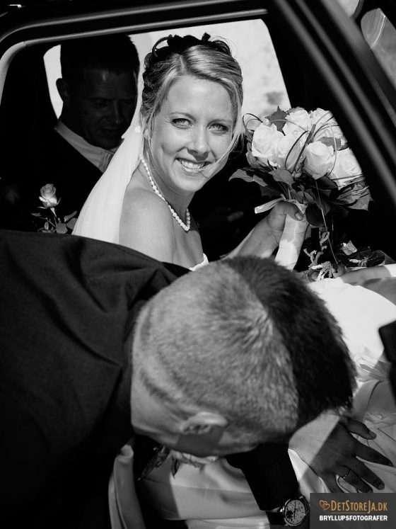 fotograf til bryllup smilende brud på vej ud af bil